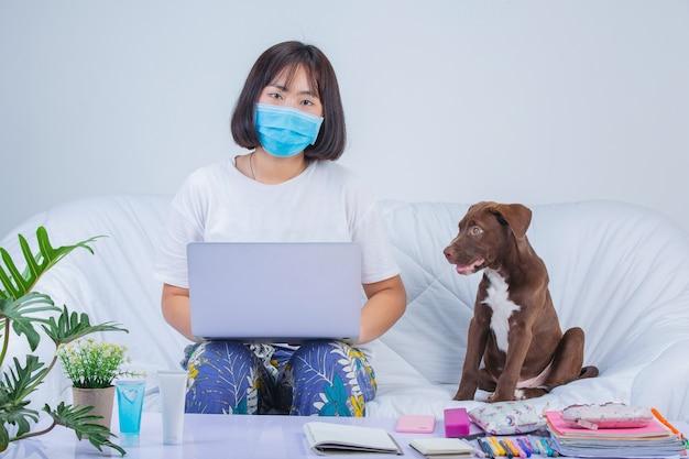 Freelancer, trabalho em casa - a jovem mulher está trabalhando perto de um cachorro em um sofá em casa.