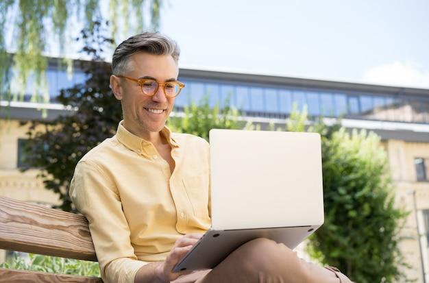 Freelancer, usando laptop, digitando. homem maduro sorridente em videoconferência