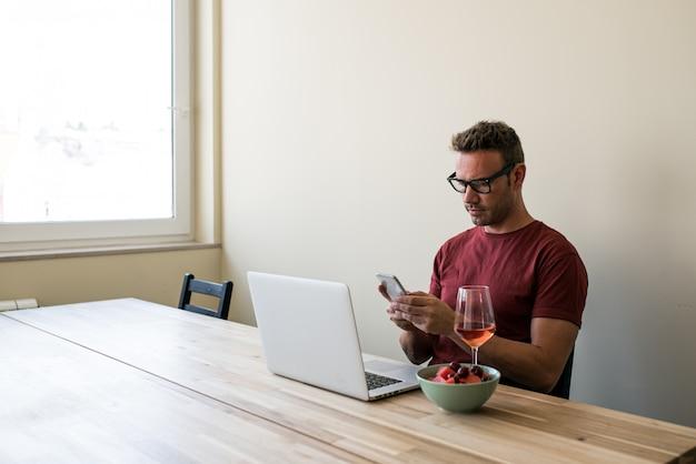 Freelancer usando laptop e celular em casa