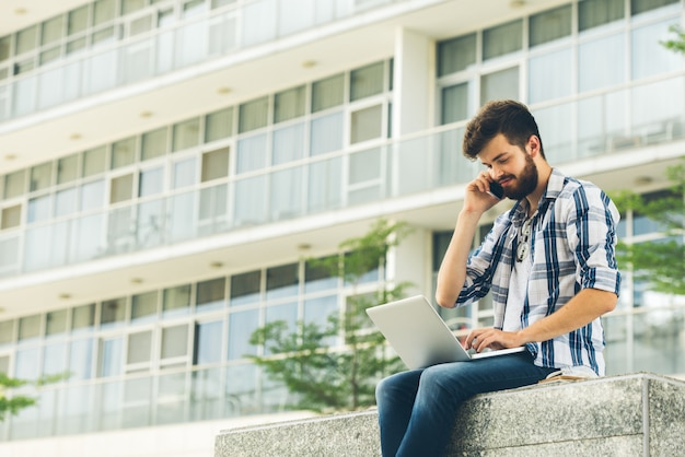 Freelancer usando laptop e telefone ao ar livre num dia de verão