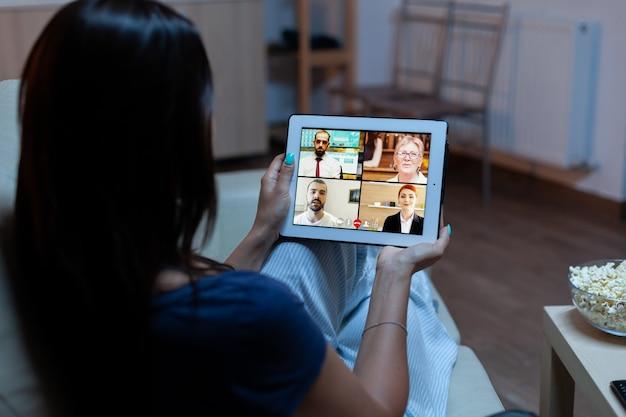 Freelancer usando tablet para videoconferência, trabalhando tarde da noite em casa