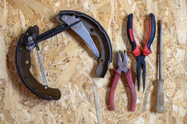 Freio de tambor do carro desmontado e um conjunto de várias ferramentas manuais de reparo ou kit de ferramentas de mecânico de automóveis em uma folha de fundo de compensado de osb. disposição plana, vista superior