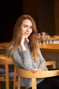 Frendly alegre e bonita mulher com cabelos longos, vestindo localização de blusa cinza na cadeira e sorrindo.