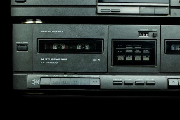 Frente a um gravador de deck de um toca-fitas cassete estéreo vintage com os botões de operação