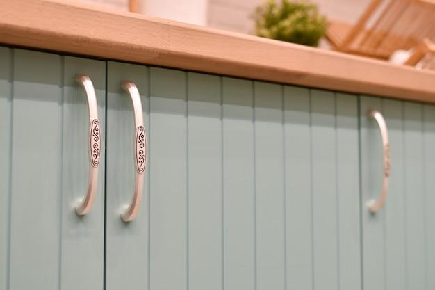 Frente azul claro do armário da cozinha com alças elegantes. parte do close-up interior da cozinha moderna.