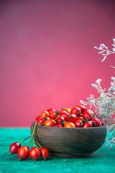 Frente bagas vermelhas dentro do prato na mesa verde-rosa baga frutas silvestres cor saudável