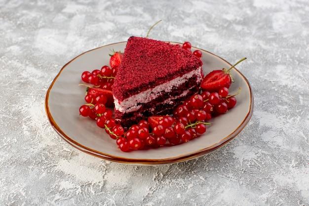 Frente bolo vermelho fatia de bolo de frutas dentro do prato com cranberries frescas em cinza