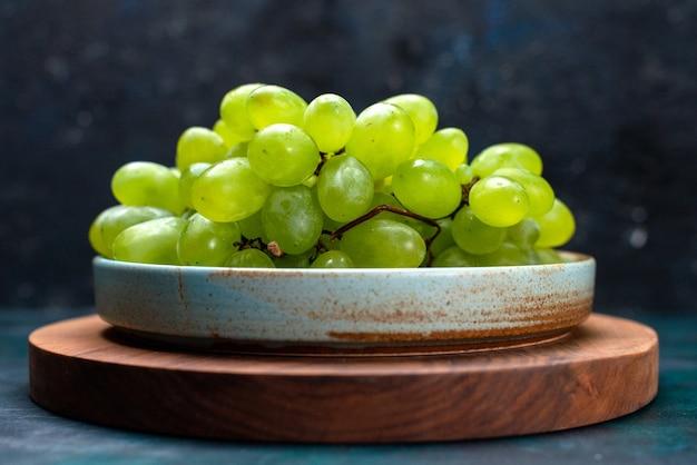 Frente close vista uvas verdes frescas frutas maduras e suculentas dentro do prato na mesa azul escuro.