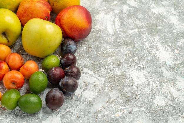 Frente com diferentes composições de frutas frutas frescas no espaço em branco Foto gratuita