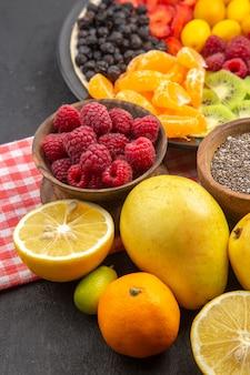 Frente com frutas fatiadas deliciosas dentro do prato com frutas frescas em árvores exóticas maduras de frutas escuras