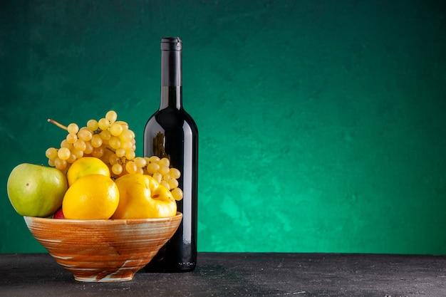 Frente com frutas frescas em uma tigela de madeira, maçãs, marmelo, limão, uvas, vinho, garrafa, ligado, verde, mesa, livre