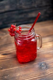 Frente com suco de cranberry fresco dentro da lata no escuro da mesa.