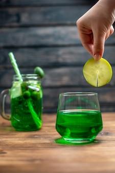 Frente com suco de feijoa fresco dentro de lata com canudo e bebida colorida de frutas em barra escura