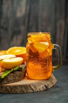 Frente coquetel corte maçãs laranjas em fundo escuro