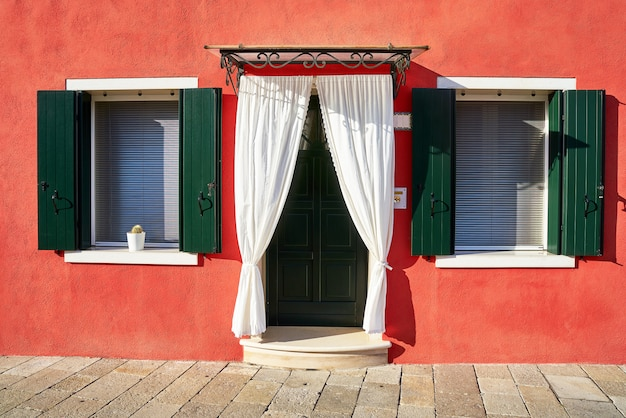 Frente da casa vermelha na ilha de burano. itália, veneza