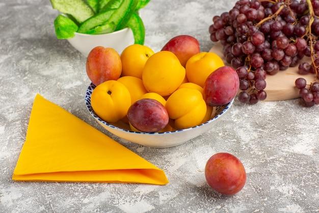 Frente, damascos doces, frutas amarelas dentro do prato com ameixas e uvas na mesa branca