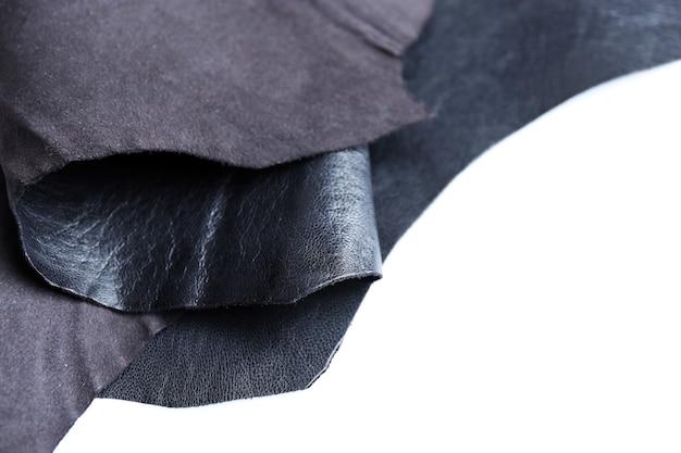 Frente de couro preto e textura do lado avesso em espaço em branco, close-up