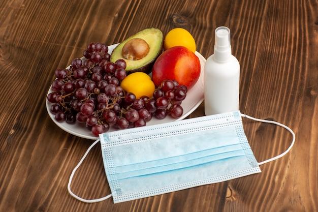 Frente de frutas diferentes com spray e máscara em mesa de madeira marrom