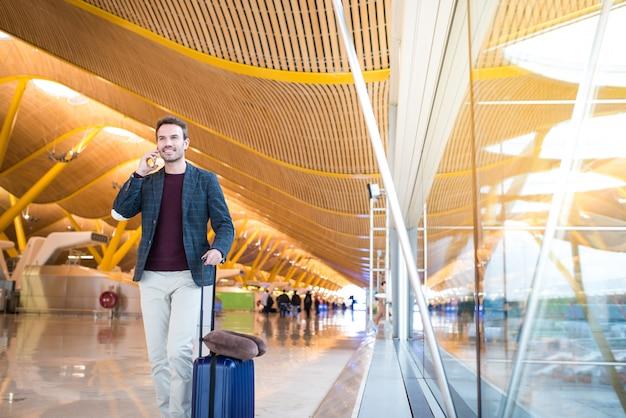 Frente de homem andando no aeroporto usando telefone celular
