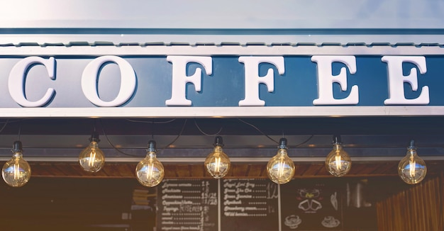 Frente de loja de café com luzes de bulbo e quadro-negro