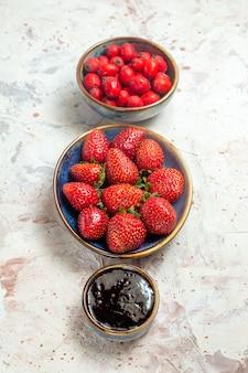Frente de morangos vermelhos frescos com frutas vermelhas em uma mesa branca frutas vermelhas frescas