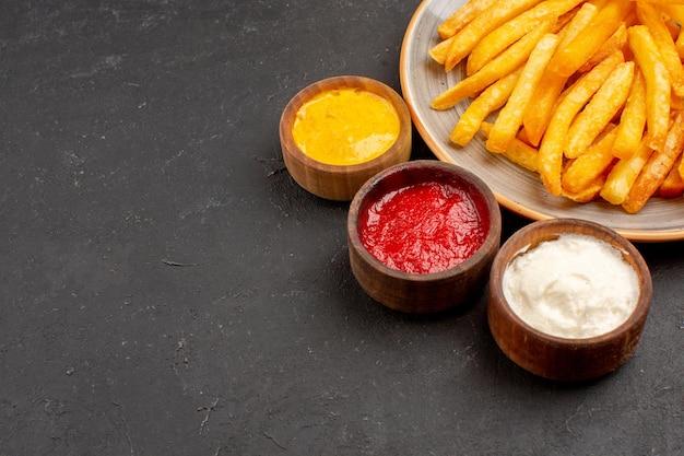 Frente de perto deliciosas batatas fritas com temperos no espaço escuro