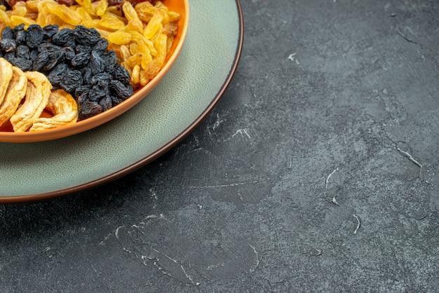 Frente de perto frutas secas com passas dentro do prato em um espaço cinza escuro