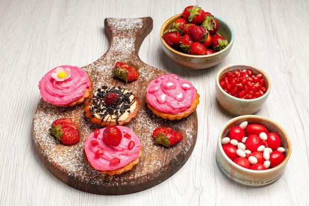 Frente deliciosos bolos de frutas sobremesas cremosas com frutas no fundo branco biscoitos cremosos sobremesa bolo doce chá