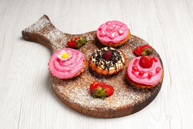 Frente deliciosos bolos de frutas sobremesas cremosas com frutas no fundo branco creme chá sobremesa biscoito bolo biscoito