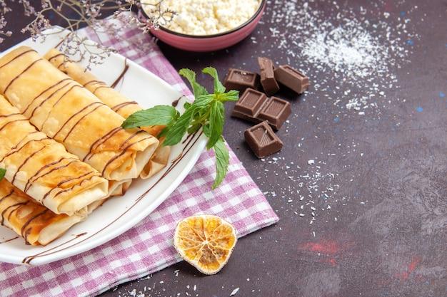 Frente deliciosos pastéis doces com barras de chocolate no espaço escuro