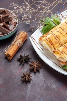 Frente deliciosos pastéis doces com chocolate no espaço escuro