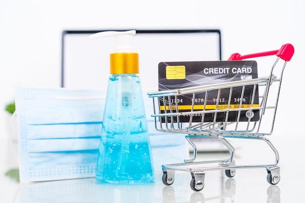 Frente do cartão de crédito da tela do laptop com desinfetante para as mãos e máscara cirúrgica para compras online, conceito de trabalho em casa de quarentena contra a epidemia covid-19