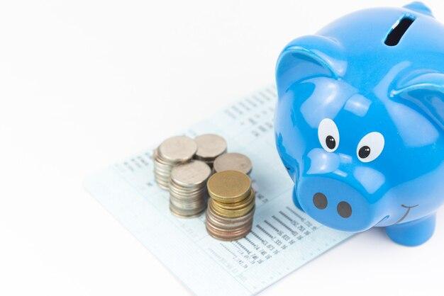 Frente do cofrinho azul com pilha de moedas no fundo branco do livro de contas