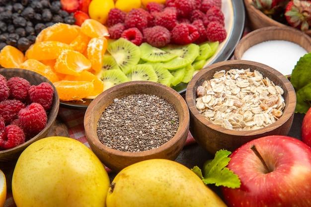 Frente, frutas fatiadas deliciosas dentro do prato com frutas frescas na árvore de fotos exóticas maduras e exóticas de frutas escuras