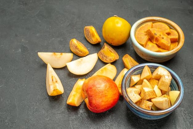 Frente, frutas fatiadas, maçãs e caquis na mesa escura, frutas frescas