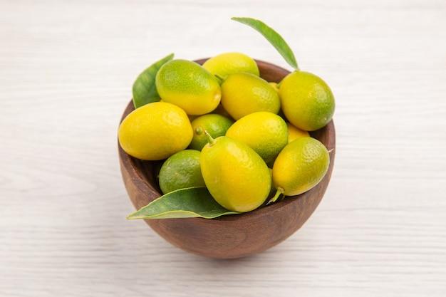 Frente frutas frescas dentro do prato no fundo branco cor fruta tropical exótica dieta madura