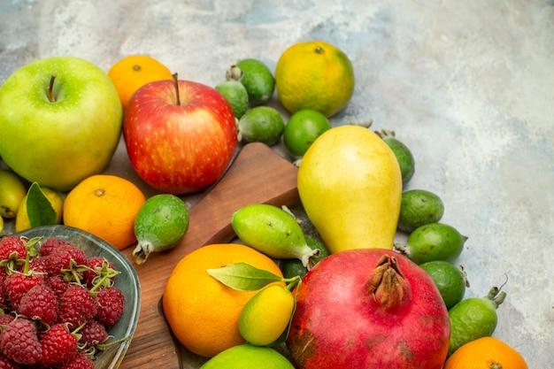 Frente frutas frescas diferentes frutas maduras e maduras no fundo branco foto saborosa dieta cor baga saúde