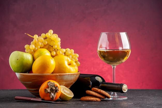 Frente frutas frescas em uma tigela de madeira maçã marmelo uvas caqui limão garrafa de vinho virada copo de vinho biscoitos na mesa vermelha