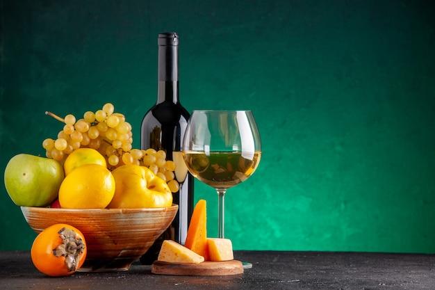 Frente frutas frescas em uma tigela de madeira maçãs marmelo uvas limão garrafa de vinho de caqui e queijo de vidro na placa de madeira na mesa verde com espaço livre