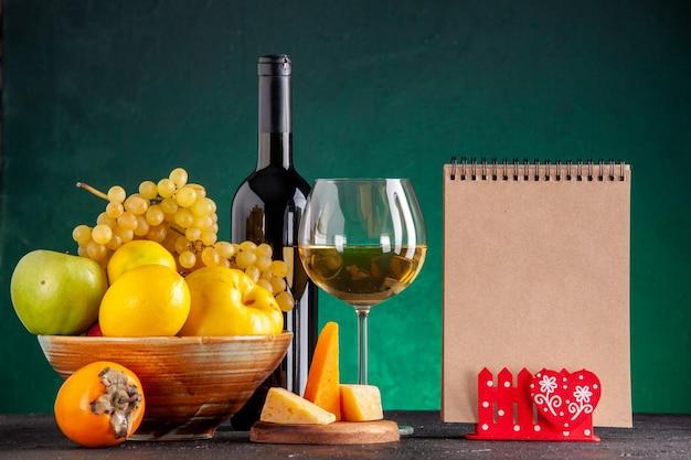 Frente frutas frescas em uma tigela de madeira maçãs marmelo uvas limão garrafa de vinho de caqui e queijo de vidro no bloco de notas de placa de madeira na mesa verde