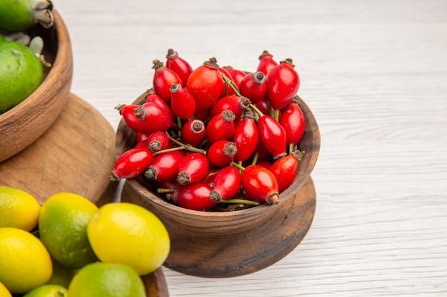 Frente frutas frescas, frutas vermelhas e feijoas em fundo branco cor de frutas silvestres foto dieta saudável