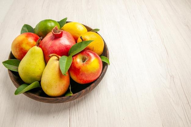 Frente frutas frescas maçãs peras e outras frutas dentro do prato na mesa branca frutas maduras árvore maduras frescas muitas