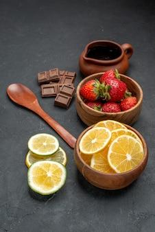 Frente, frutas frescas, morangos e limões no fundo cinza