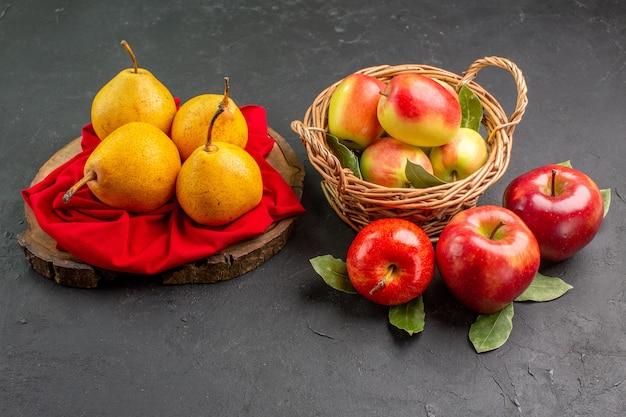 Frente, frutas frescas, pêras e maçãs na mesa escura, maduras de cor fresca