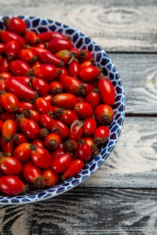 Frente frutas vermelhas frescas maduras e frutas ácidas dentro da placa na superfície cinza árvore de vitaminas da cor das frutas vermelhas