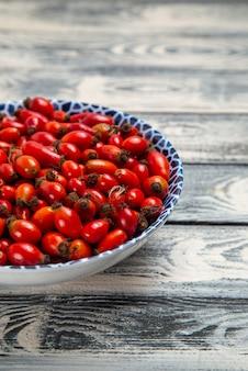 Frente frutas vermelhas frescas maduras e frutas ácidas dentro do prato na superfície cinza