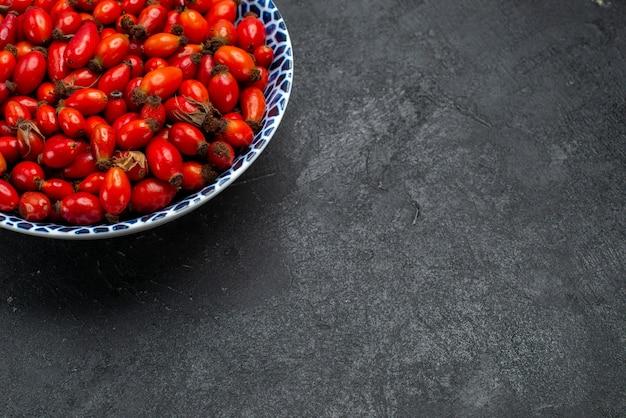 Frente frutas vermelhas maduras e frutas ácidas dentro do prato na mesa cinza