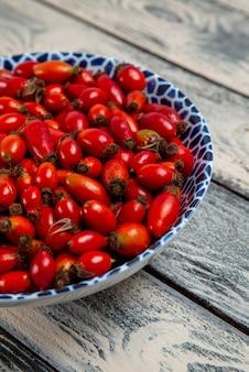 Frente frutas vermelhas maduras e frutas ácidas na planta de árvore vitamínica cinza de superfície