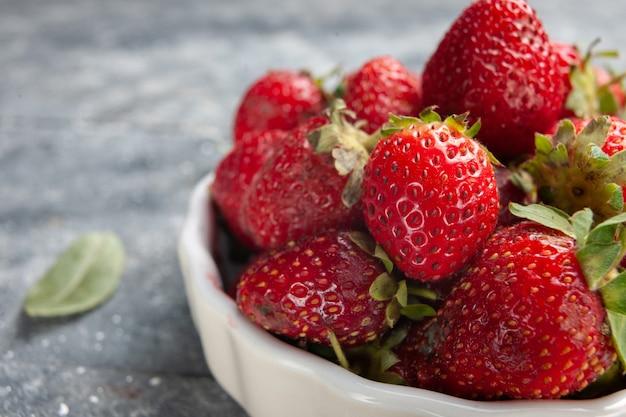 Frente mais de perto morangos vermelhos frescos dentro de um prato branco junto com folhas verdes secas na mesa cinza