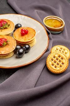 Frente panquecas deliciosas com azeitonas e frutas em um bolo de frutas doce de superfície escura